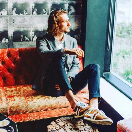 בחור בלונדיני עם שיער ארוך מתבונן בחלון נועל נעליים לגברים