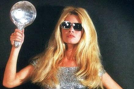 אישה בלונדינית בחולצת כסף ומשקפי שמש מחזיקה פלאש