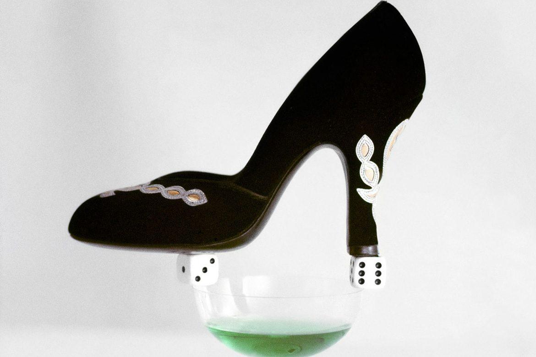 נעל עקב שחורה מאוזנת על קוביות משחק שמאוזנות על כוס עלת פתח רחב