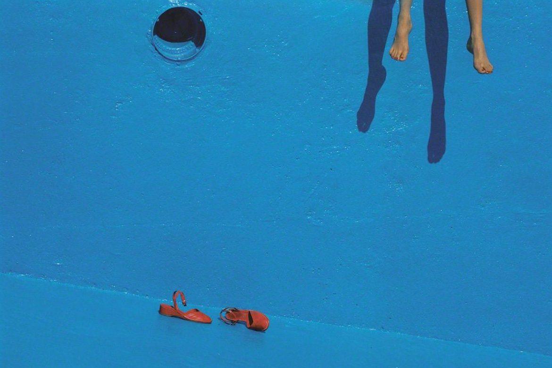 בריכה כחולה, נעלים בקרקעית, רגליים מטילות צל על הקיר