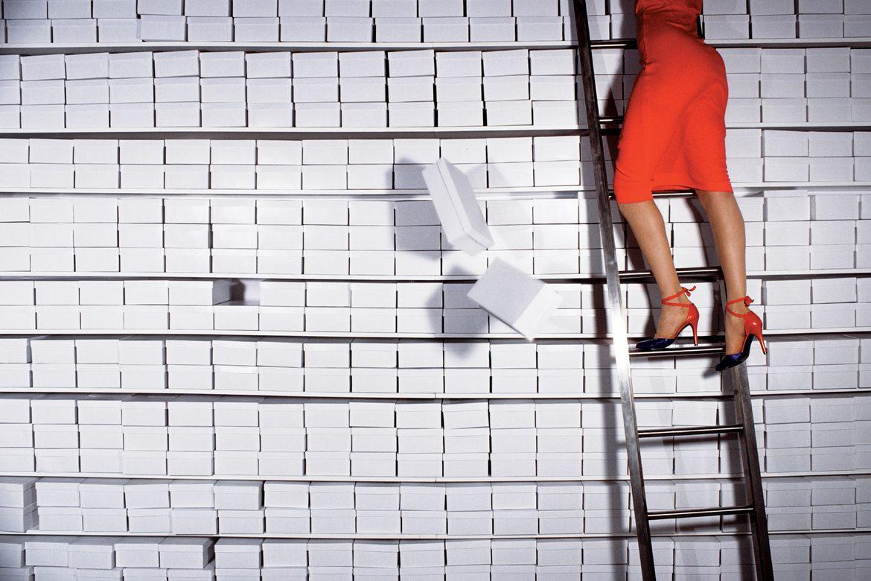 אישה בשמלה אדומה על סולם בעליה, קופסאות נעליים נופלות מטה