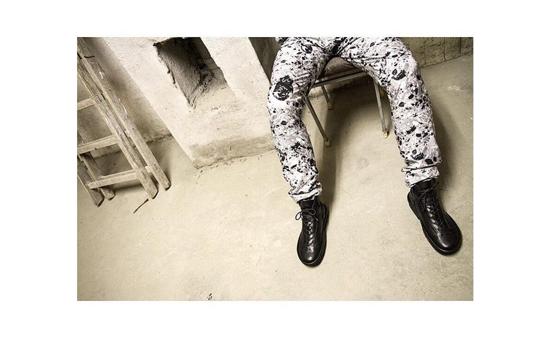 נעלי טריפן (Trippen) שחורות עם שרוכים על בחור עם מכנסיים בצע לבן עם כתמים אפנתיים