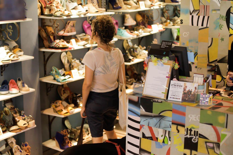 אישה מתבוננת בדגמים בחנות שופרא שינקין