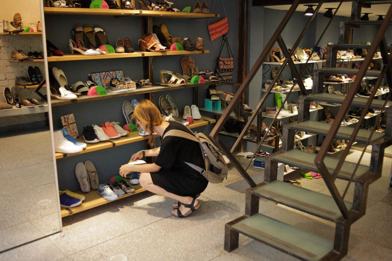 נערה בלבוש שחור מחפשת את זוג הנעליים שיתאימו לה במדפי החנות של חנות הנעליים בשינקיןסיור מצולם בשופ שופרא ברחוב שנקין בתל אביב