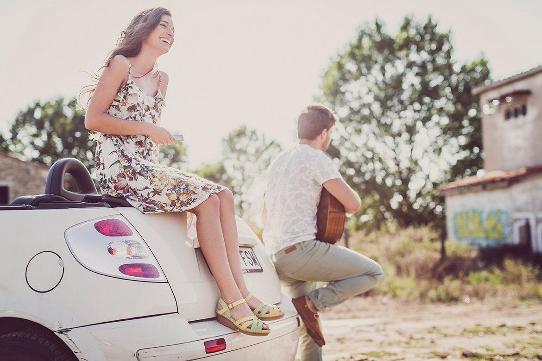 אישה יושבת על החלק האחרוי של רכב וצוחקת בעוד גבר שנשען על הרכב מנגן בגיטרה לכיוון ההפוך שלה