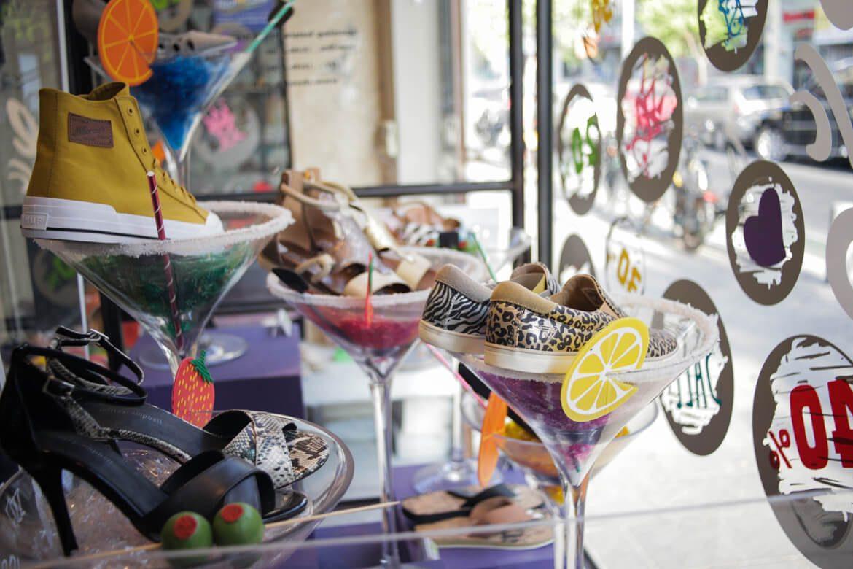 נעליים שונות יושבות בתוך כוסות קוקטייל בחלון ראווה של סניף שנקין תל אביב בשופרא