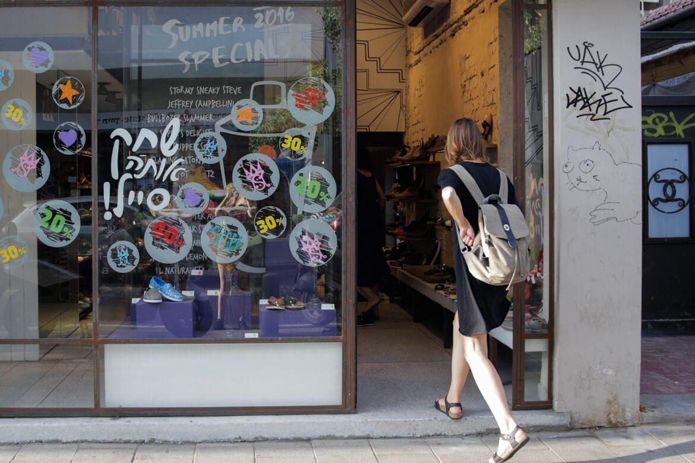 אישה נכנסת לחנות שופרא ברחוב שינקין בזמן סייל