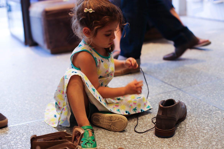 ילדה בשמלה משחקת על רצפת חנות נעליים עם שרוך נעל חומה