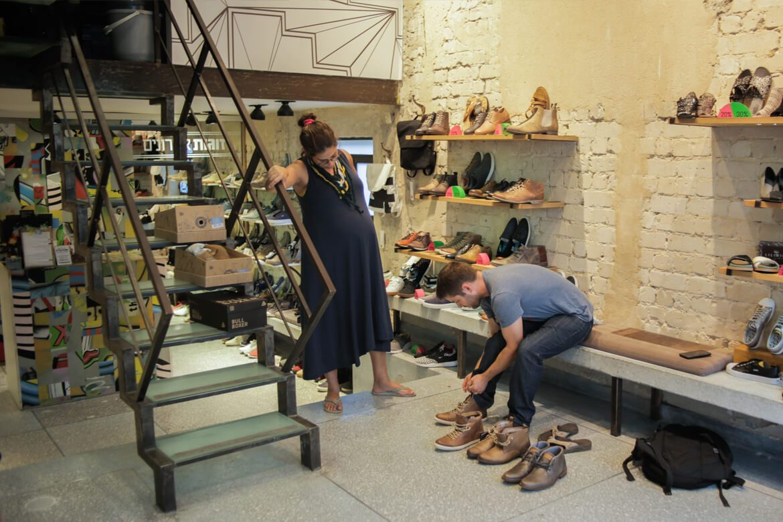 מבקר בחנות הנעליים של שופרא מודד זוג נעליים לגבר בעוד זוגתו צופה בו ומנסה להבין מה דעתו