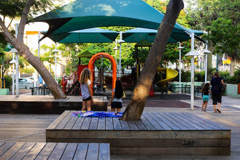 שתי ילדות בגינה הציבורית אל מול מתקני המשחקים
