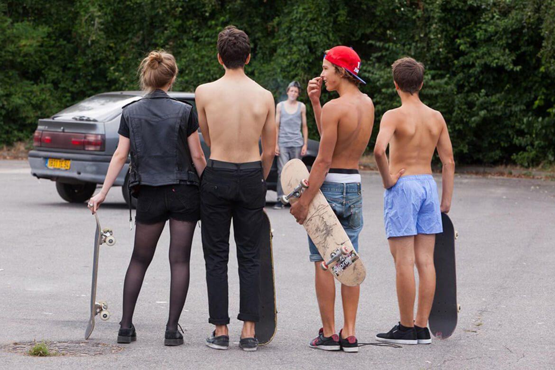 גלריה | הסקייטרים של לארי קלארק | Kids-1995 | ילדים עומדים במגרש חניה ומסתכלים. כולם עם סקייטבורדים.