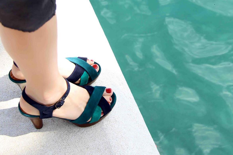 נעלי צ'י מיהארה על שפת בריכה לבנה, נעולות על ידי אישה עם לק אדום בציפורני הרגליים שלה