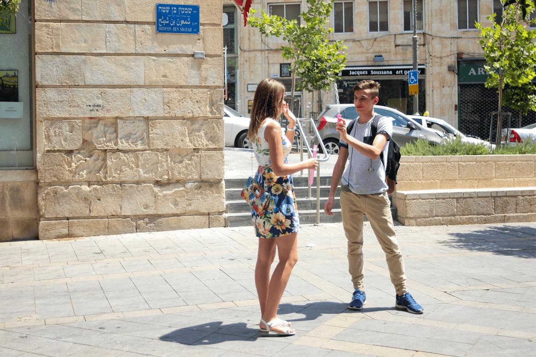 זוג צעיר מחזיקים שני חלקים של מתקן להפרחת בועות ברחוב שמעון בן שטח בירושלים