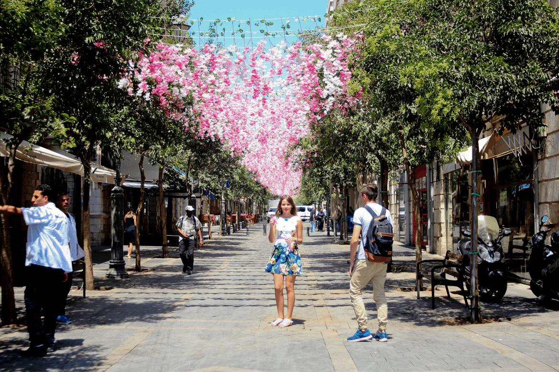 נערה עומדת במרכז רחוב ירושלמי כשמעליה פריחה נעימה.