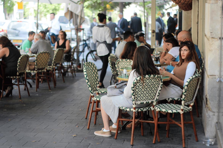 אנשים יושבים בבית קפה ירושלמי, מישהי מתבוננת במצלמה בחשד בעוד חברה שלה לא שמה לב