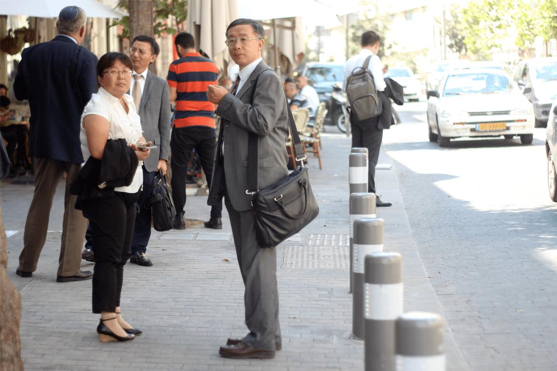 איש עסקים יפני עם תיק צד ברחוב שלומציון בירושלים עם זוגתו