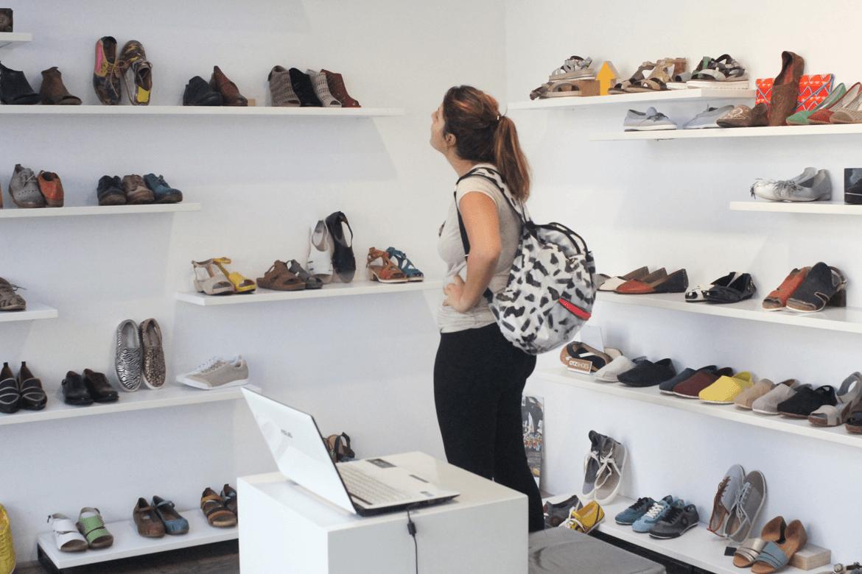 אישה מתבוננת בדגמי הנעליים שעל מדפי הקירות בסניפי שופרא