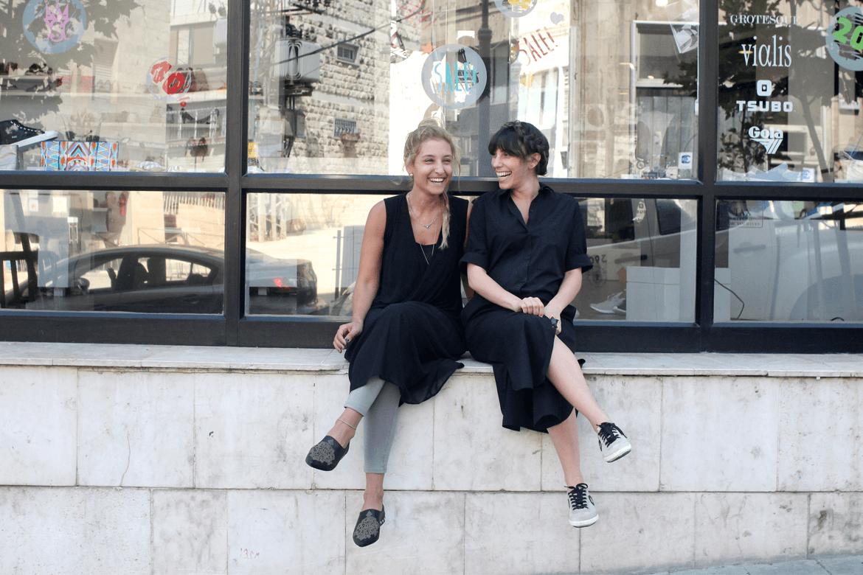 שתי נשים יושבות על אדן וצוחקות מחוץ לסניף הנעליים של שופרא בשלומציון המלכה, ירושלים