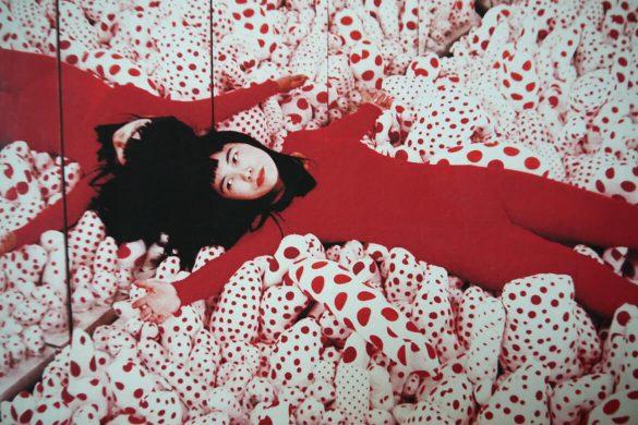 יאיוי קוסמה שוכבת על כריות בצבעי אדום ולבן