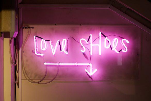שלט ניאון ורוד שמצהיר על אהבת הנעליים של בעל השלט