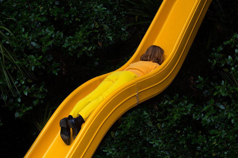 צילום - ילדה לבושה בצהוב על מגלשה צהובה